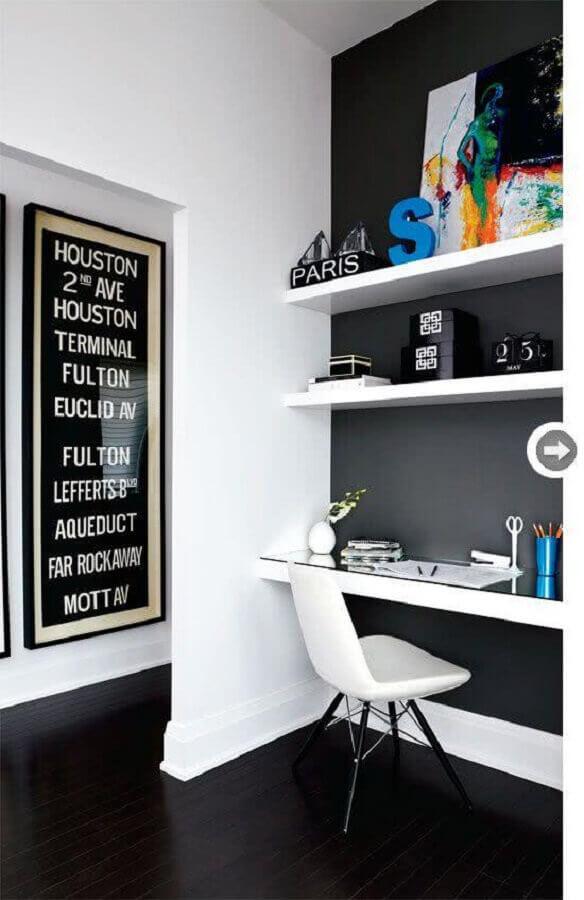 home office decorado com parede preta e prateleiras e bancada branca Foto Achados de Decoração