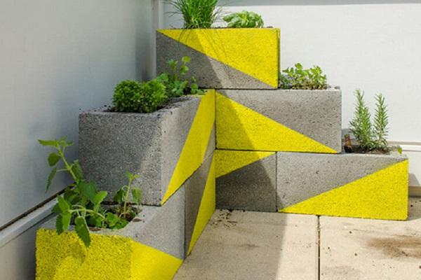 Bloco de concreto com pintura amarela como vasos