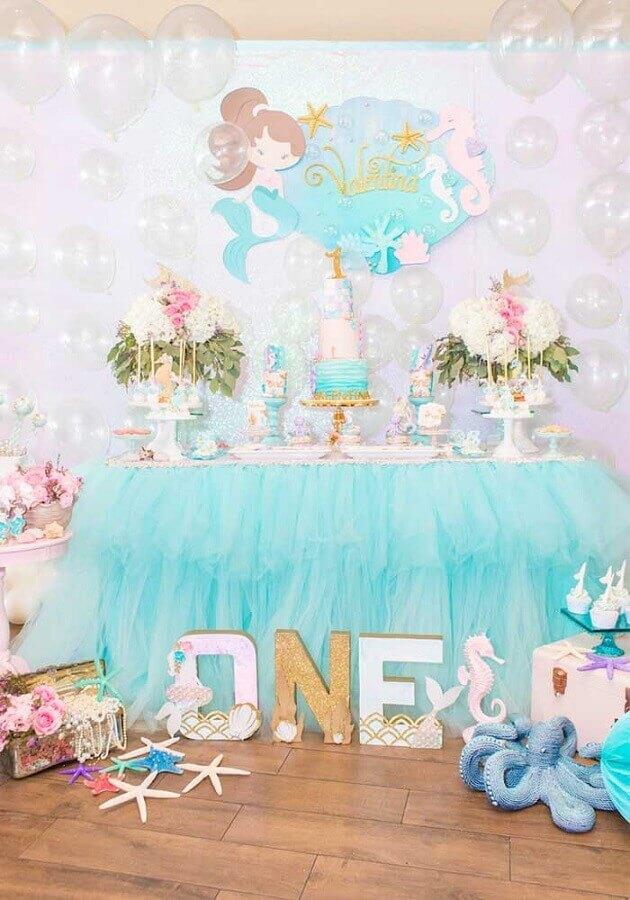 mesa de festa infantil sereia decorada com babado azul e balões transparentes  Foto Pinterest