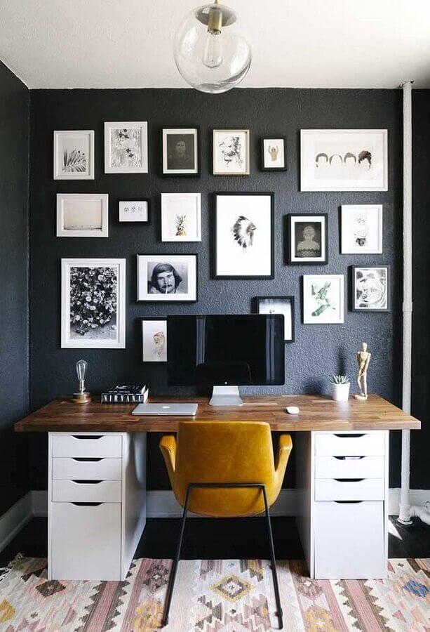 mesa home office decorado com parede preta cheia de quadros Foto TrendYideas