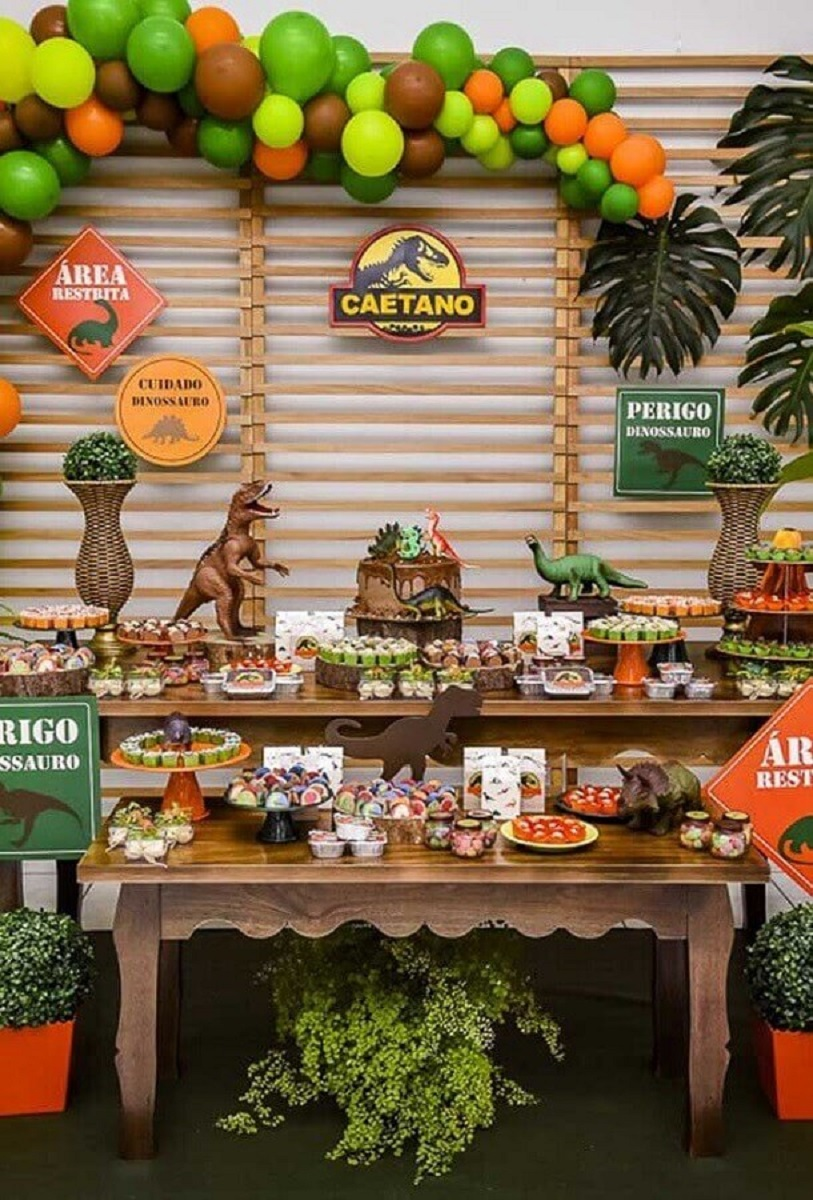 wooden panel decorated with colorful leaves and balloons for children's party dinosaurs Photo Golosinas de La Costa