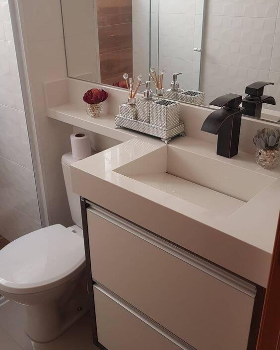 Pia esculpida de mármore no banheiro decorado