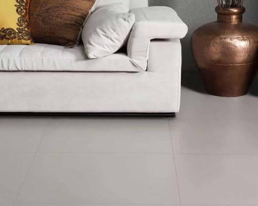 Porcelanato cinza com sofá bege