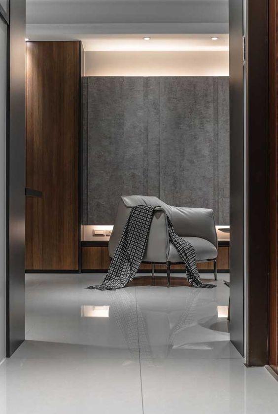 Porcelanato cinza polido no quarto de casal com poltrona combinando