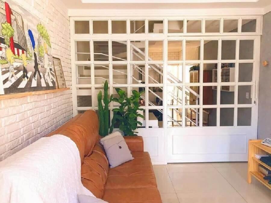 porta de correr para sala pequena com parede de tijolinho pintada de branco Foto Morada Dois