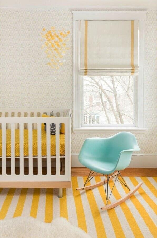quarto de bebê amarelo decorado com cadeira de balanço azul e tapete listrado Foto Mandarina Studio