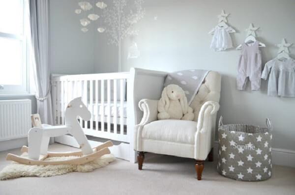 quarto de bebê cinza e branco com cabides suspensos