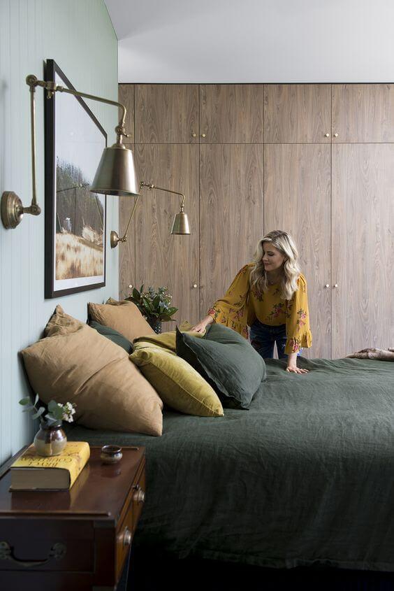 Quarto verde com armário e móveis de madeira