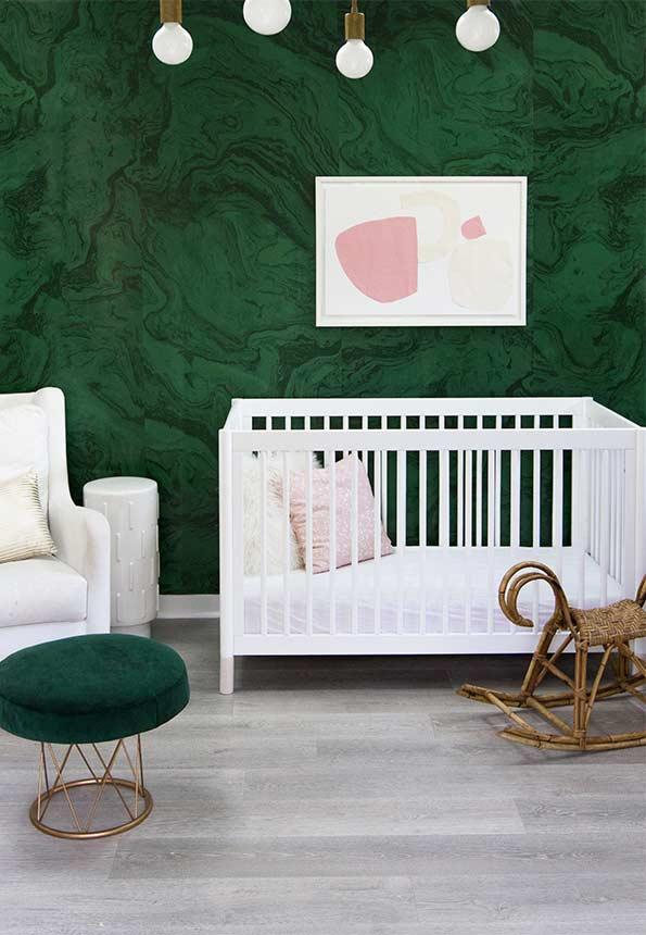 Quarto com papel de parede verde e móveis brancos