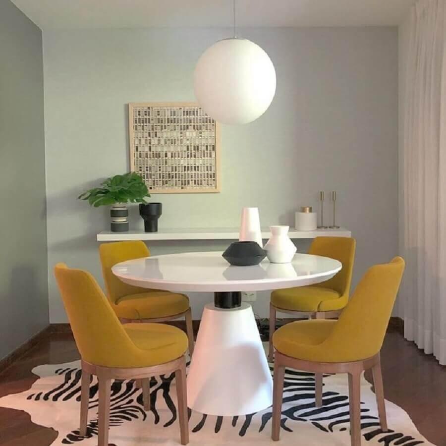 sala de jantar com mesa branca redonda e cadeiras cor mostarda Foto Roberto Bobl