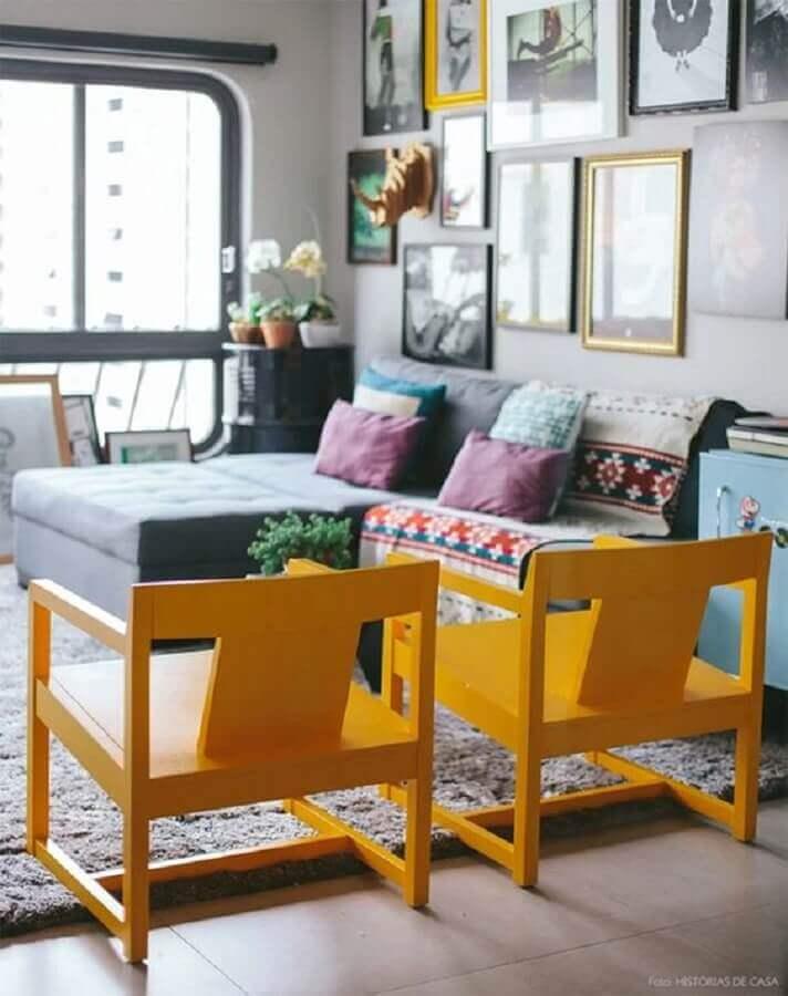 sala decorada com cor mostarda e vários quadros na parede Foto Casinha Arrumada