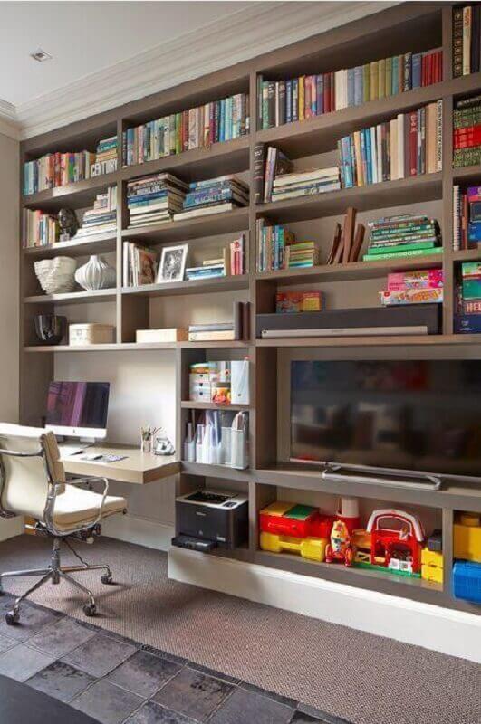 sala decorada com estante de nichos planejada com home office Foto Elgin & Ellis