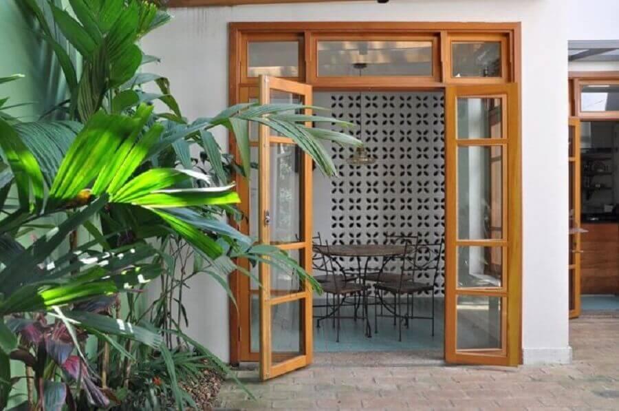 área externa decorada com porta francesa de madeira e vidro Foto Luciana Manzano