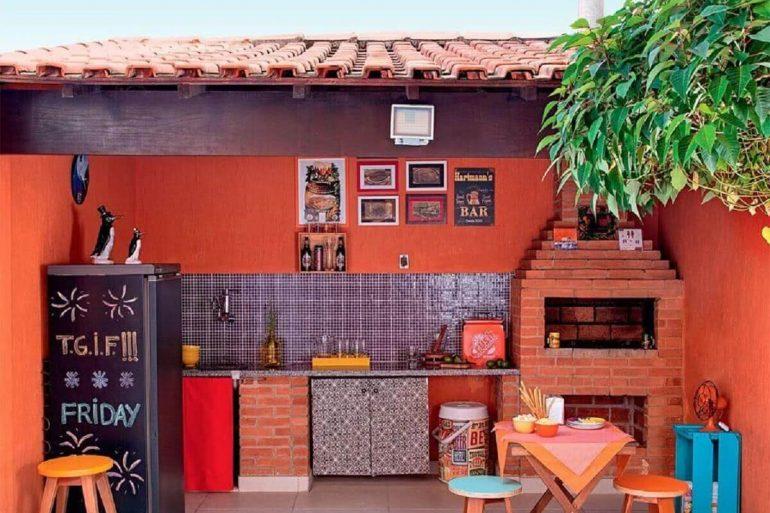 área gourmet simples com churrasqueira de tijolinho e geladeira preta  Foto Otimizi