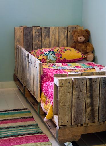 A cabeceira de pallet e o suporte lateral protegem a criança na cama infantil
