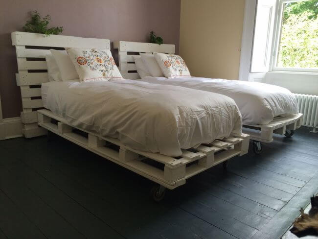 A cabeceira de pallet que compõe a decoração desse quarto recebeu acabamento branco