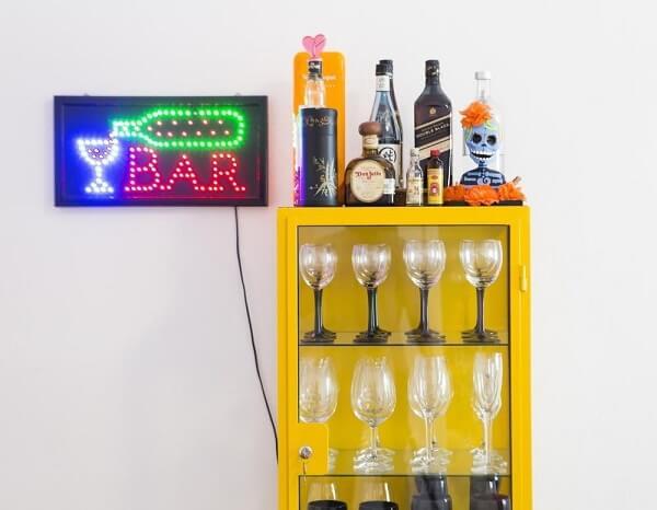 A cristaleira amarela trouxe um charme especial para o home bar