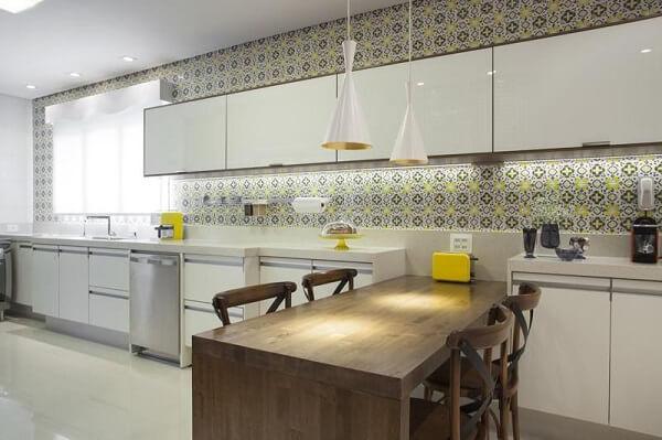 A parede com ladrilho e as cadeiras de madeira para cozinha trazem um charme a parte
