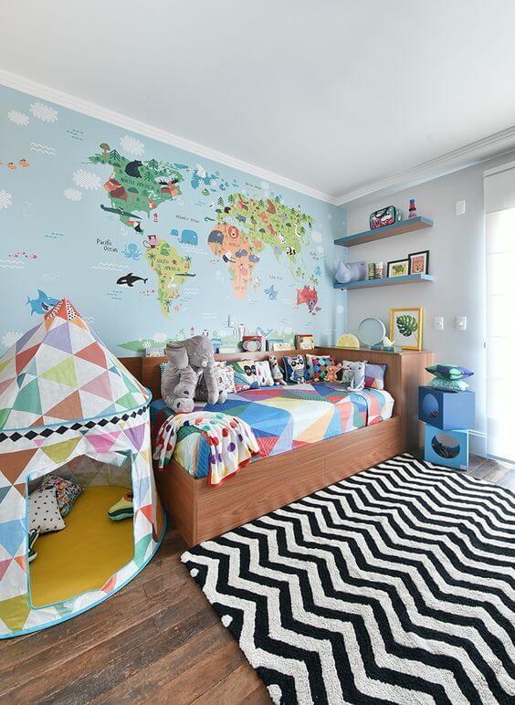 A parede com mapa mundi se destaca no quarto com cama de madeira