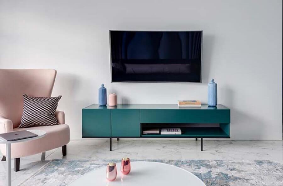 A poltrona cor de rosa e o rack azul decoram a sala de estar