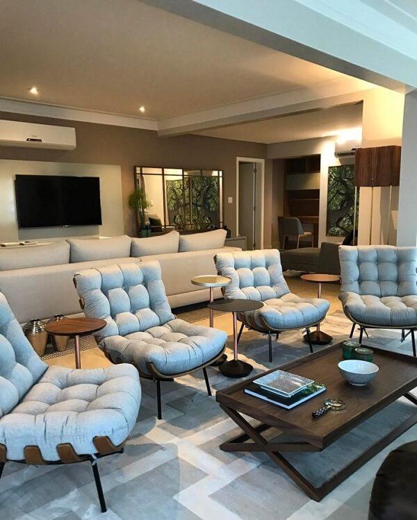 A poltrona costela forma uma linda divisória de ambientes, separando sala de estar e sala de tv