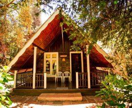 As cadeiras brancas da varanda do chalé d emadeira convidam para a contemplação do jardim.