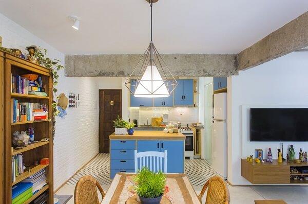 As cadeiras de madeira se harmonizam com os móveis em tom azul