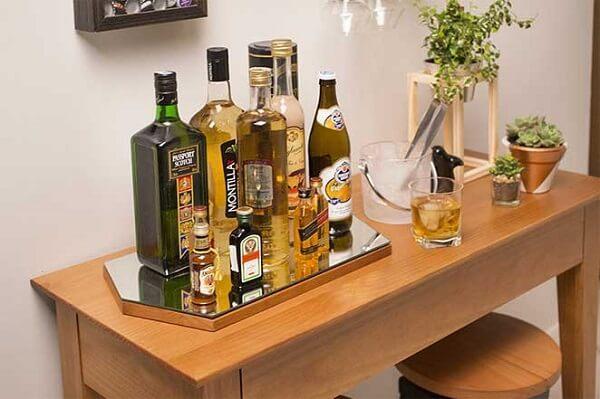 As garrafas foram organizadas sobre uma bandeja espelhada