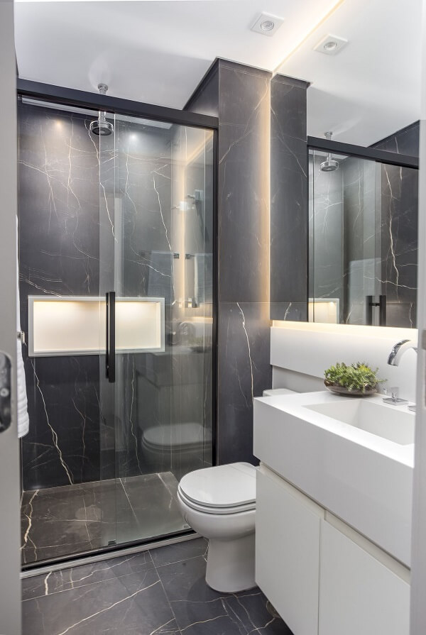 Banheiro sofisticado com box transparente e revestimento escuro. Fonte: Altera Arquitetura