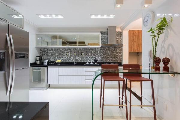 Cômodo planejado com pastilhas de vidro e cadeira alta para cozinha