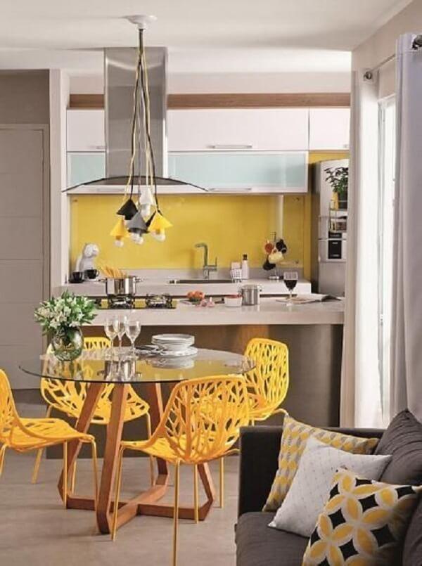 Cadeiras para cozinha amarelas e pendentes metálicos coloridos trazem vida para o ambiente