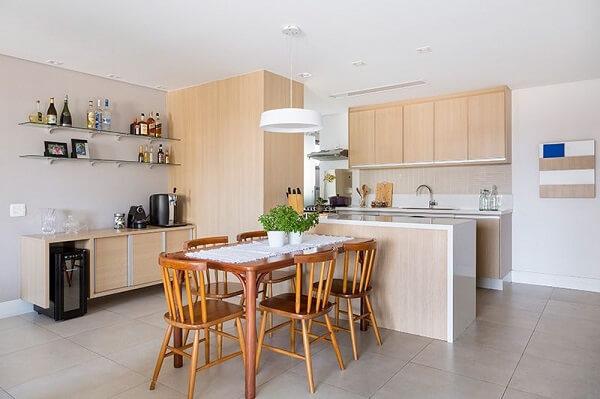 Cadeiras para cozinha de madeira e pendente decoram o espaço