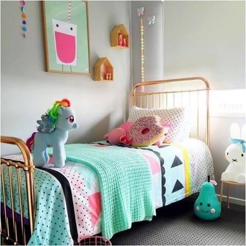 Cama metálica dourada e decoração infantil azul