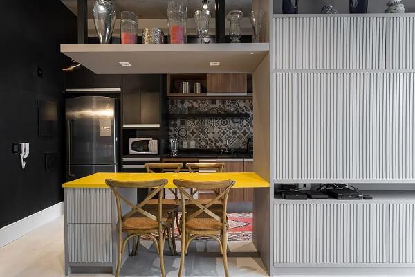 Cozinha com mesa amarela e cadeiras de madeira de demolição