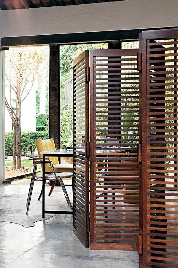 Crie uma separação parcial do ambiente incluindo um biombo de madeira vazado