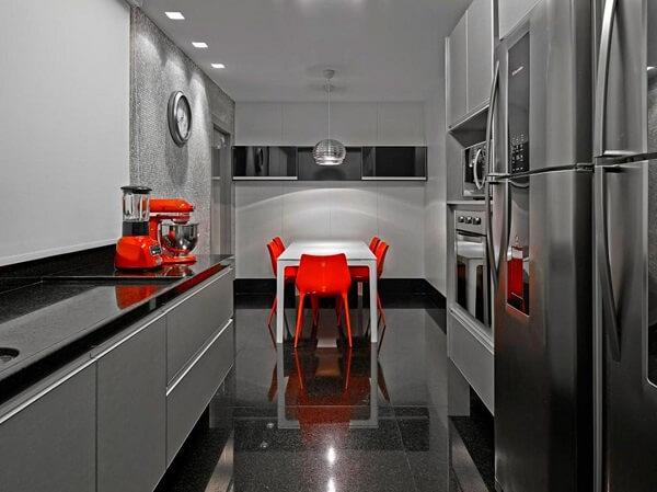 Móveis em marcenaria cinza e cadeiras acrílicas na cor laranja