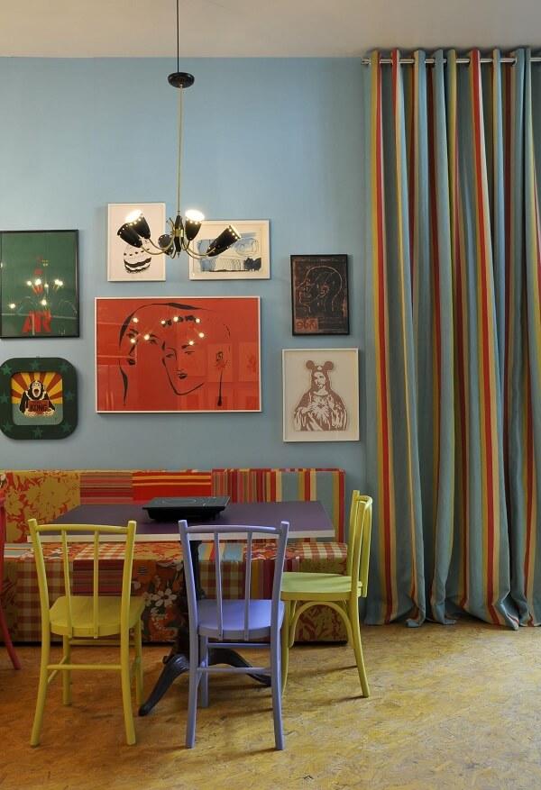 Mesa azul e cadeiras coloridas para cozinha alegram o ambiente