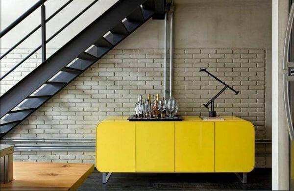 Nesse ambiente o home bar foi montado sobre o buffet amarelo