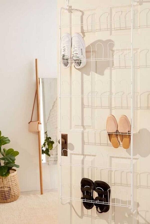 O aramado branco simples acomoda diversos sapatos na porta