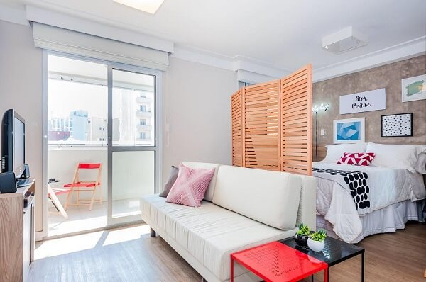 O biombo de madeira vazado auxilia na separação dos cômodos de apartamentos tipo lofts