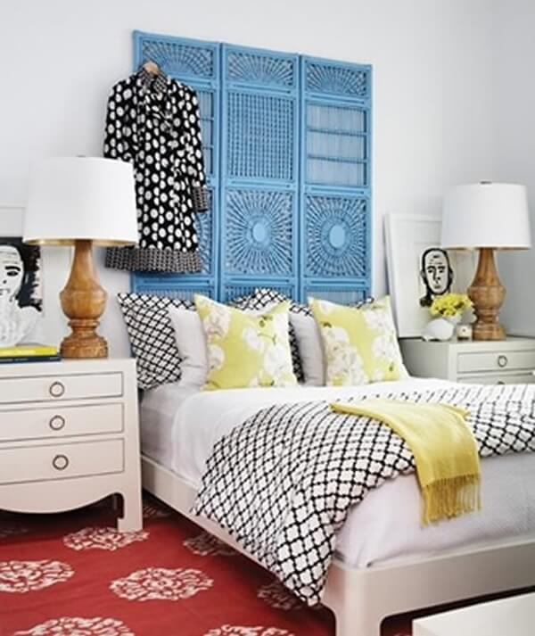 O biombo de madeira azul foi usado como cabeceira da cama de casal