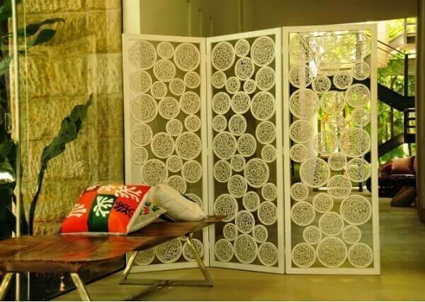 O biombo de madeira branco divide ambientes da casa
