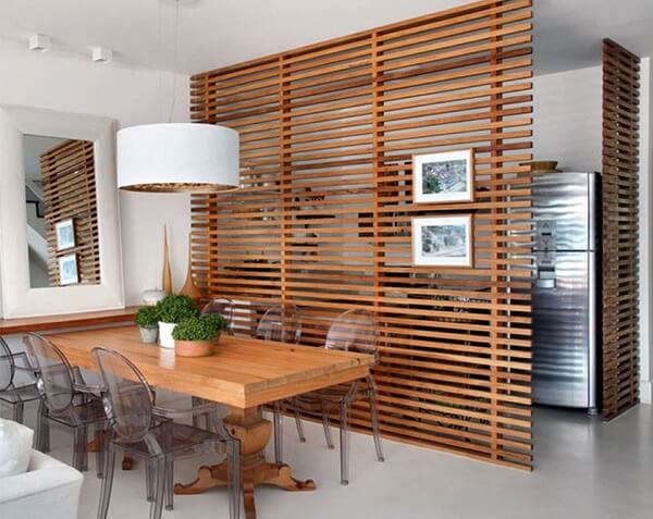 O biombo de madeira com ripas separa a cozinha da sala de jantar