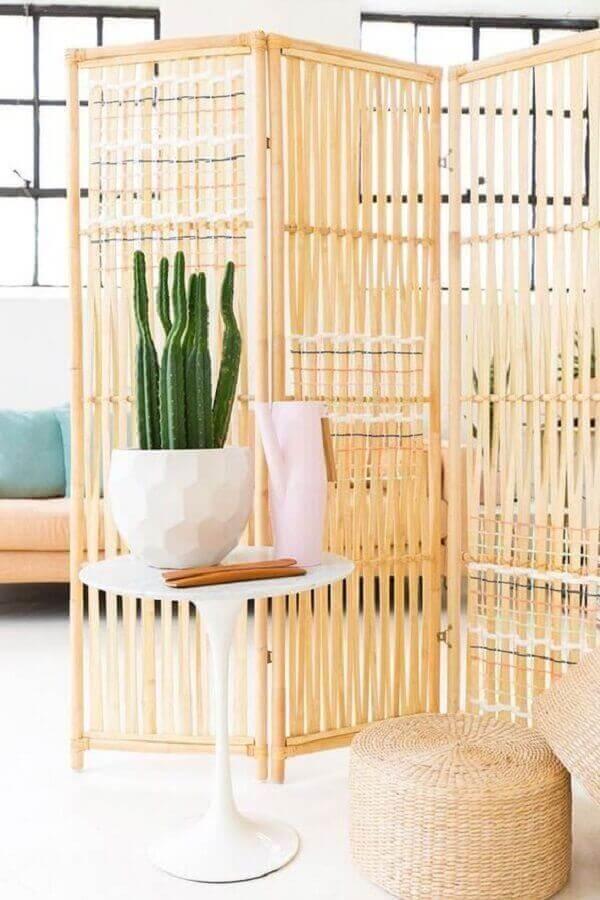O biombo de madeira complementa a decoração da sala de estar com leveza