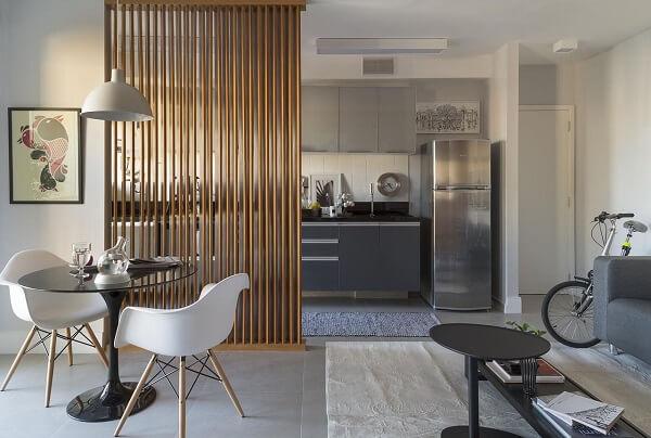O biombo de madeira fixo separa parcialmente os ambientes da casa