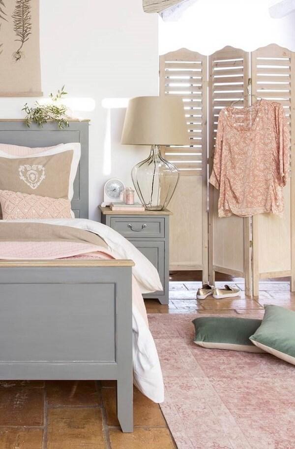 O biombo de madeira traz leveza para o quarto de casal