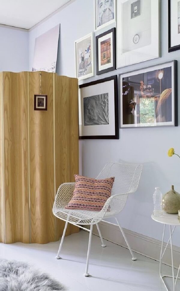O biombo de madeira traz privacidade em um dos cantos do cômodo