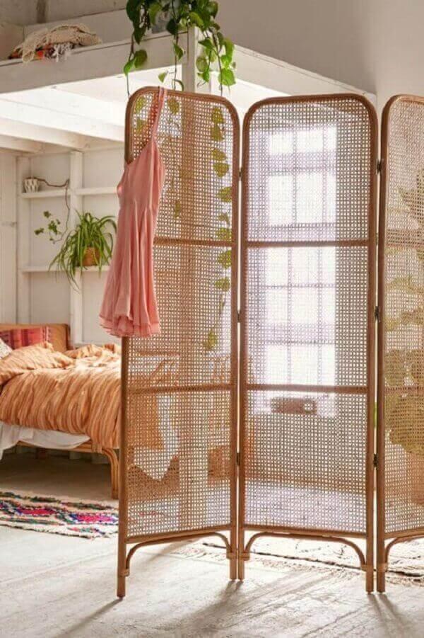 O biombo de madeira treliça decora com elegância o quarto de casal