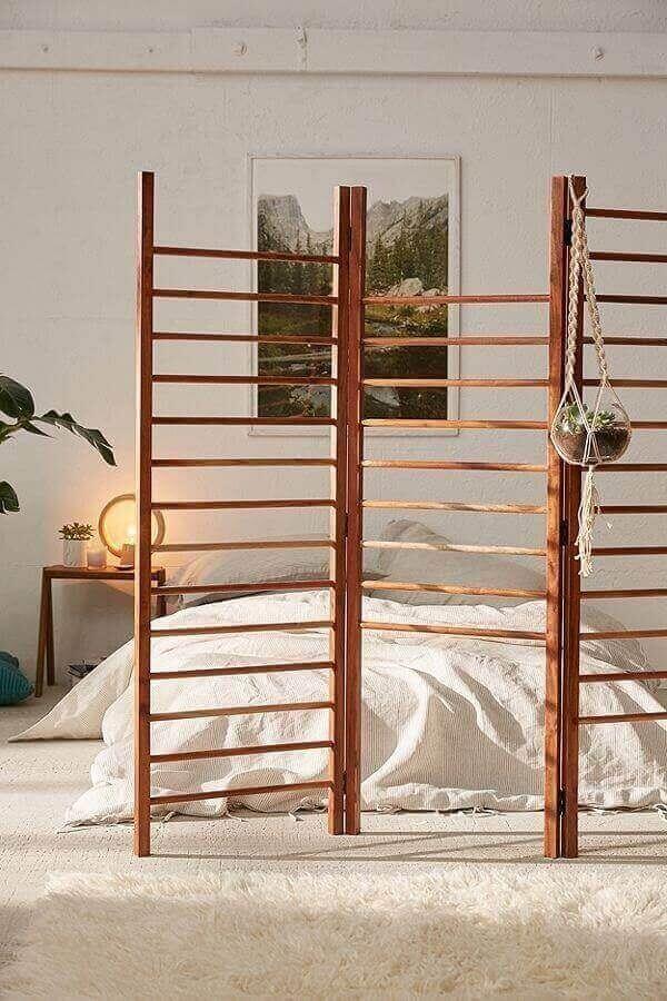 O biombo de madeira vazado tem função decorativa no quarto de casal