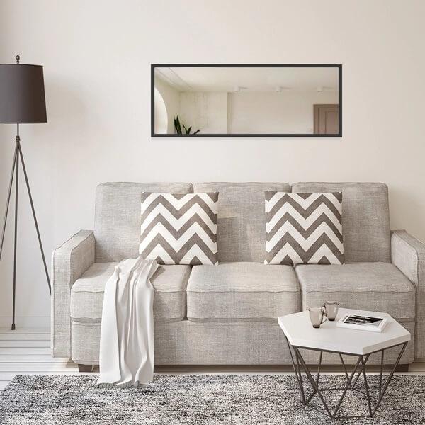 O espelho com moldura preta se harmonização com a decoração da sala de estar